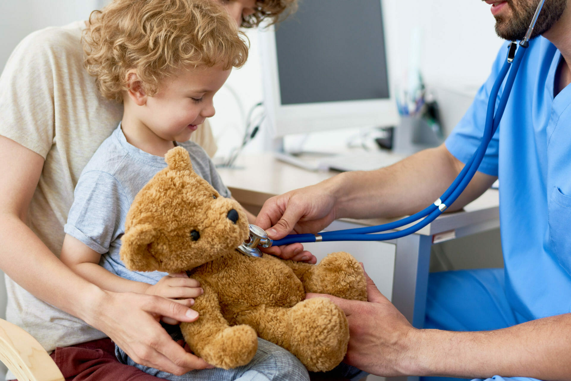 Portrait of adorable curly child  sitting on mothers lap in doctors office holding teddy bear toy, with pediatrician listening to heartbeat using stethoscope